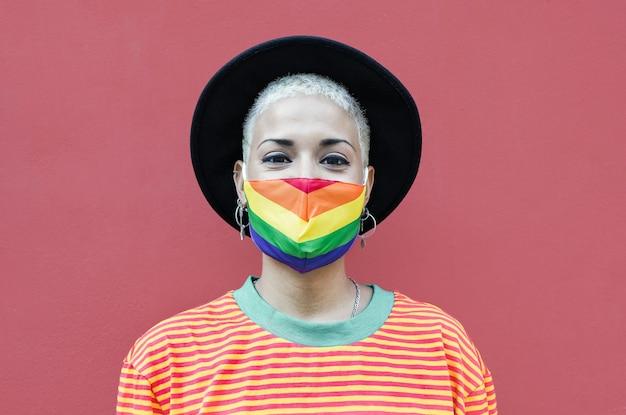 コロナウイルスの発生のためにレインボーフェイスマスクを身に着けている幸せなゲイの女性-同性愛の愛の概念