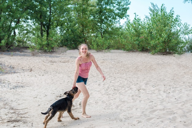 Happy german shepherd puppy and beautiful blonde girl have fun running on the beach and playing on the sand on a sunny summer day by the river. the concept of walking and playing with a dog in nature