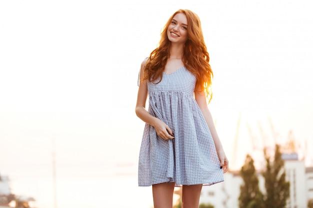 Счастливая рыжая девушка в платье позирует на закате