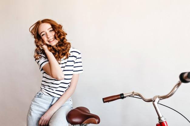 Ragazza felice dello zenzero in posa vicino alla bici e ridendo. ritratto di splendida giovane donna con l'acconciatura riccia che gode del servizio fotografico con la bicicletta.