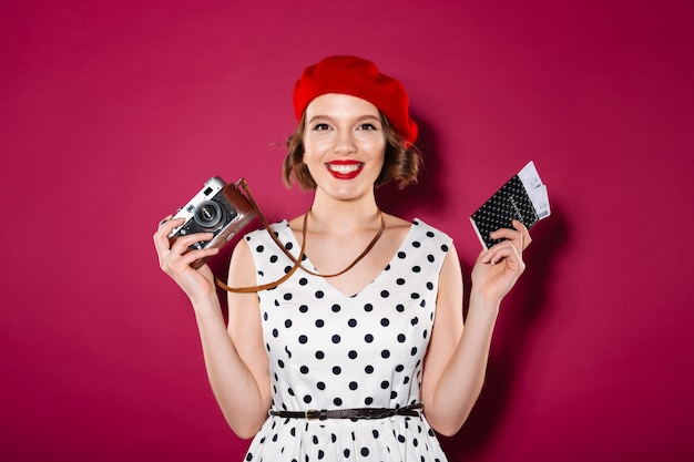 Happy ginger woman in dress holding passport with tickets and retro camera while looking at the camera over pink