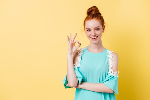 Happy ginger woman in dress showing ok sign
