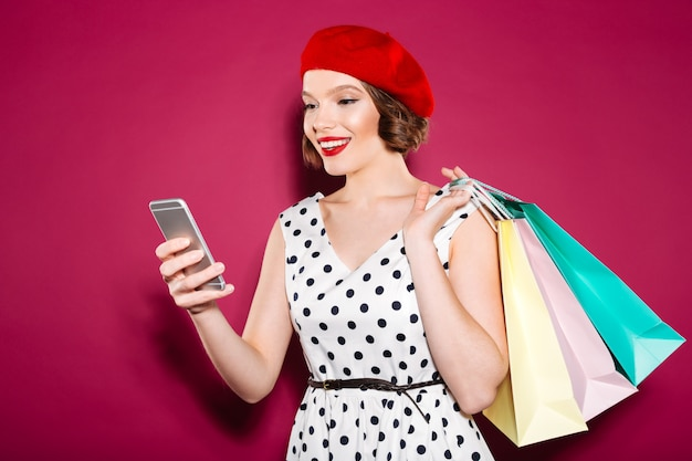 Happy ginger woman in dress with packages using smartphone over pink