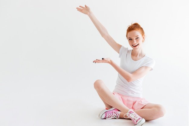 Happy ginger woman girl sitting on the floor and showing something