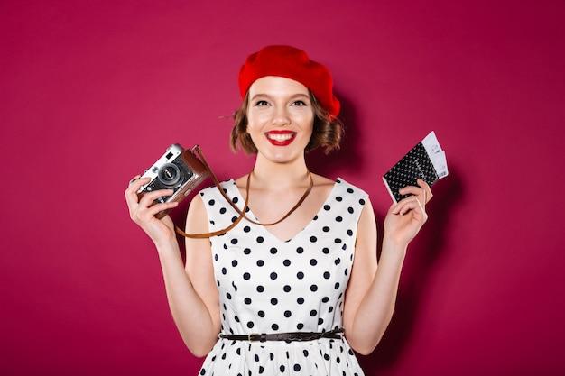 Счастливая рыжая женщина в платье держит паспорт с билетами и ретро-камеру, глядя на камеру над розовым