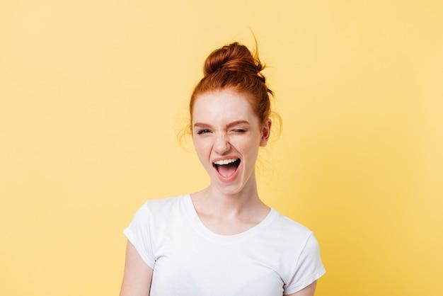 Счастливая рыжая женщина в футболке подмигивает