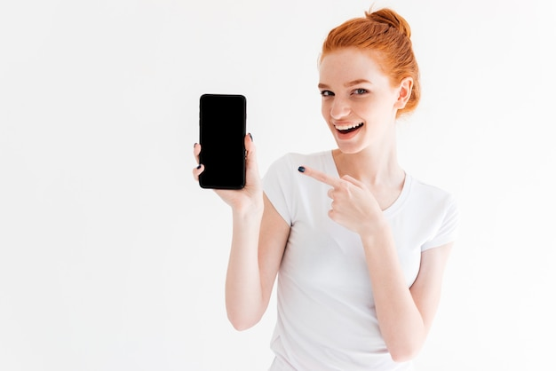 Happy ginger woman showing blank smartphone screen and pointing at him