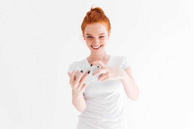 Happy ginger woman in t-shirt playing on her smartphone