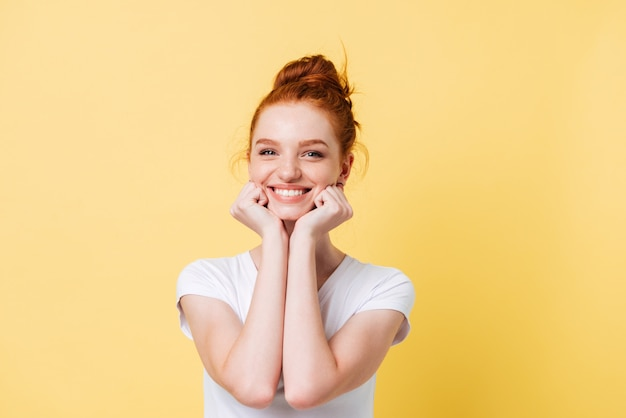Happy ginger woman in t-shirt reclines on hands