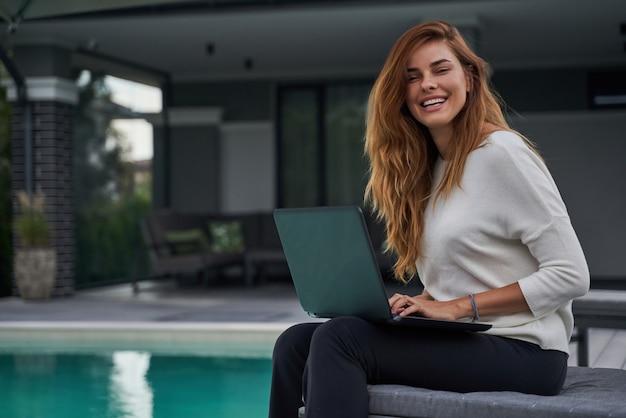 화창한 날 수영장 가장자리에서 노트북을 사용하는 행복한 생강 여성. 수영장 근처 아파트에서 프리랜서로 일합니다. 기술 개념