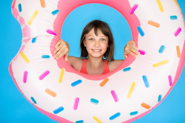 Happy girl 10 years old with straw hat in swimsuit with swimming ring donut on a colored blue wall