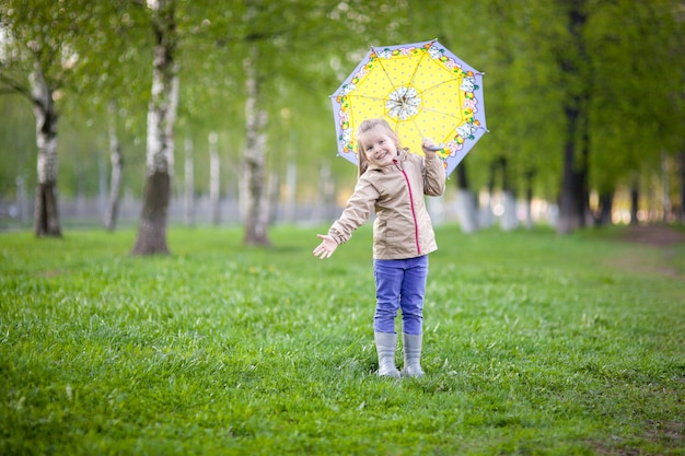 Happy girl 5 years under a yellow umbrella walks on the green grass after the rain