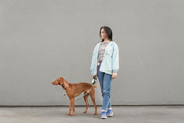 幸せな少女と灰色の壁に対して茶色の犬。