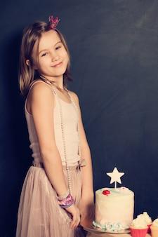 誕生日パーティーで幸せな女の子とカップケーキ
