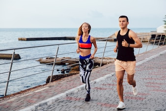 Happy girl and guy jogging together on the quay near the sea. Sport concept.