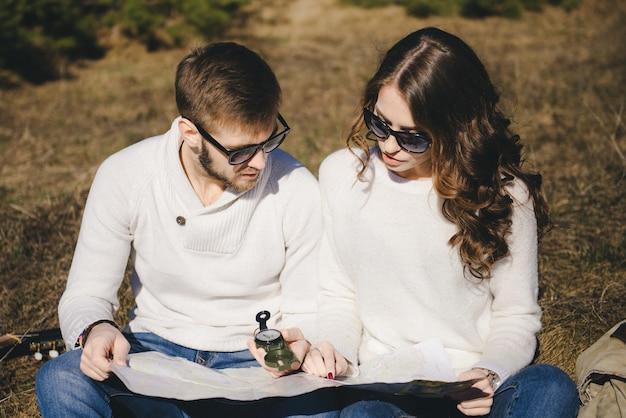 Счастливая девушка и парень с туристическим рюкзаком и гитарой, глядя на маршрут с компасом и картой, концепция истории любви, выборочный фокус