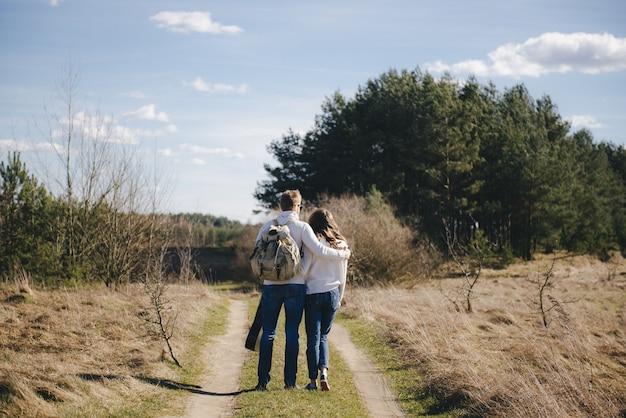幸せな少女と観光バックパックと自然の中を歩いてギターを持つ男旅行愛物語コンセプト、セレクティブフォーカス