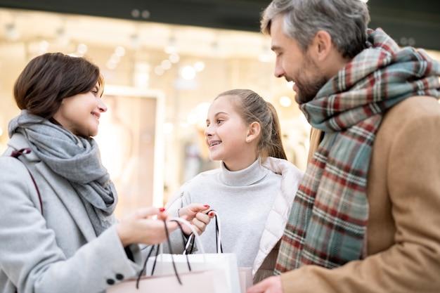 幸せな女の子と彼女の母親が買い物袋を買った後、買い物をしながらお互いを見つめる