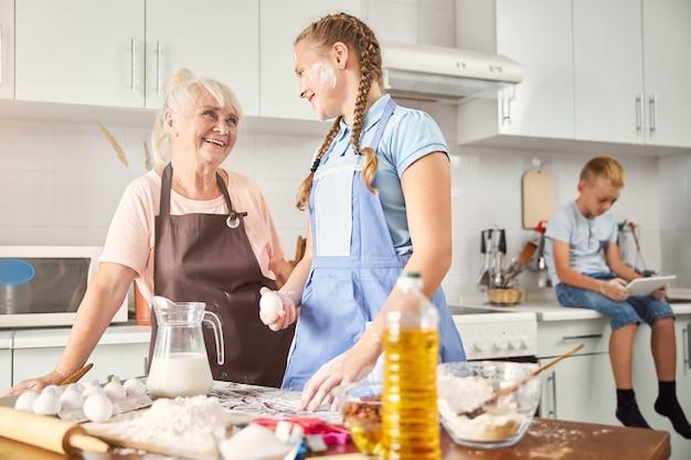 행복한 소녀와 그녀의 웃는 할머니가 부엌에서 포즈를 취하고 있다