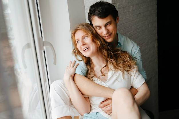 행복 한 여자와 남자 집에서 창 근처 포옹. 흰색과 파란색 옷. 발렌타인 데이.