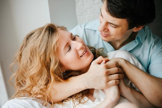 幸せな女の子と男が家の窓の近くで抱き締めます。白と青の服。バレンタインデー。