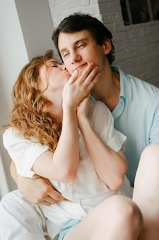 행복 한 여자와 남자 집에서 창 근처 키스. 흰색과 파란색 옷. 발렌타인 데이.