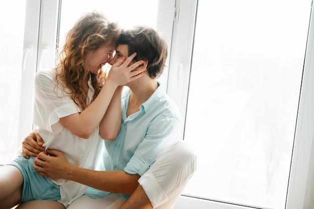 幸せな女の子と男が家の窓の近くでキスします。白と青の服。バレンタインデー。
