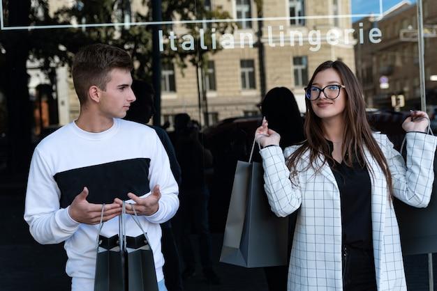Счастливая девушка и усталый парень после покупок. молодая женщина с покупками в руках. пара возле окна магазина.