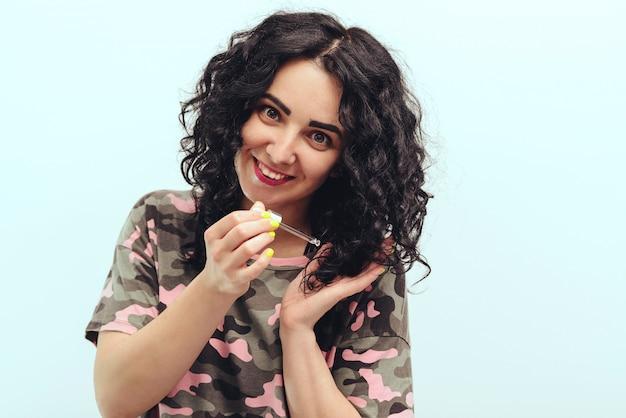 Счастливая девушка, применяя натуральное масло на кончиках ее вьющихся волос в домашних условиях