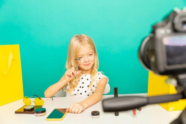집에서 행복 한 소녀 vlog에 대 한 카메라 앞에서 말하기. 블로거로 일하는 어린 아이, 인터넷 용 비디오 튜토리얼 녹화.