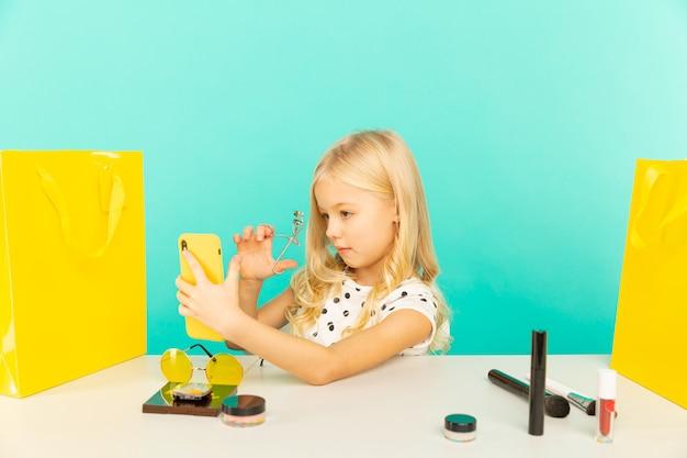 Счастливая девушка дома, говоря перед камерой для видеоблога. маленький ребенок работает блогером, записывает видеоурок для интернета.