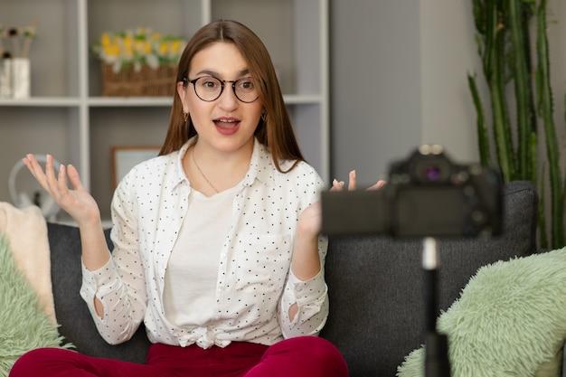 Счастливая девушка у себя дома говорить перед камерой. люди и технологии, молодая женщина на работе, как влоггер. веб-авторитетная запись сообщения для интернет-социальных сетей