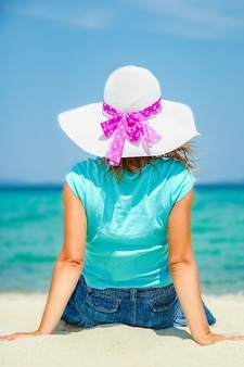 砂の自然のギリシャの海で幸せな女の子