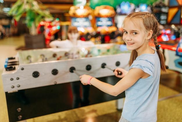 Счастливая девушка в настольный футбол в детском игровом центре
