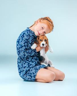La ragazza felice e un cucciolo di beagle su sfondo grigio