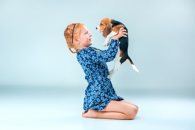 The happy girl and a beagle puppy on gray wall