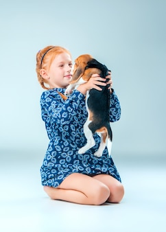 The happy girl and a beagle puppy