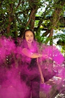 幸せな女の子、自然光、選択的な焦点と色の煙棒を持つ美しい幸せな女の子。