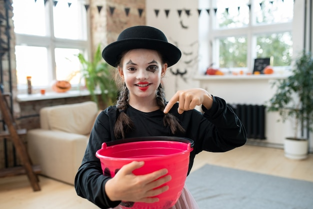 Happy girl in black attire asking for halloween treats