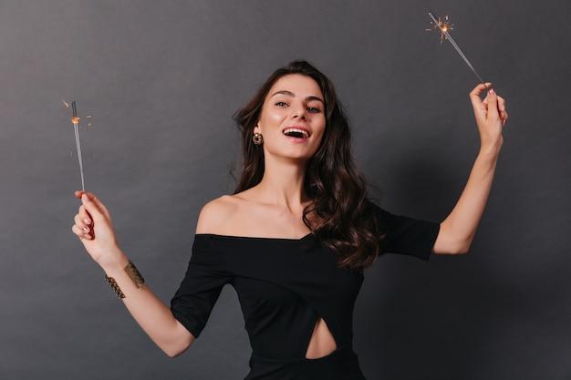 Felice ragazza in abito nero con un enorme braccialetto sul braccio sta godendo le vacanze e posa con le stelle filanti.