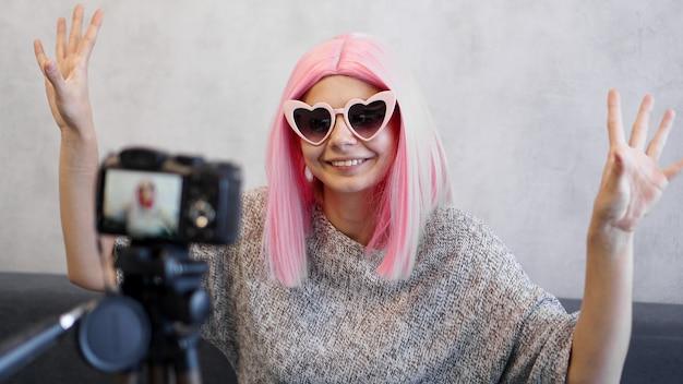 三脚のカメラの前にピンクのかつらで幸せな女の子のブロガー。彼女はビデオブログを録画し、ソーシャルネットワーク上のサブスクライバーと通信します。