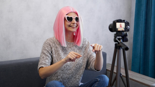 Happy girl blogger in pink wig in front of the camera on a tripod. she records a video blog
