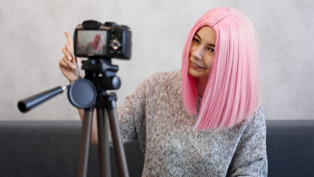 Happy girl blogger in pink wig in front of the camera on a tripod