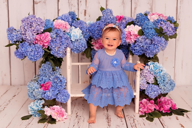 Happy girl in blue dress sits on bed with blue and pink hydrangea flowers
