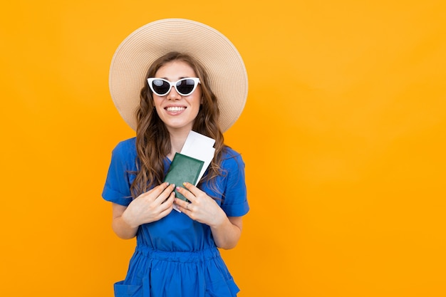 Happy girl in a blue dress and a straw hat and sunglasses with a passport and vacation tickets on yellow with copy space