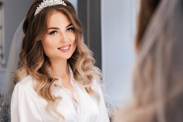 Счастливая девушка-невеста с макияжем и укладкой улыбается перед зеркалом на утреннем сборе в день свадьбы
