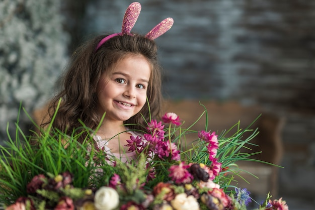 Happy girl in bunny ears with flowers