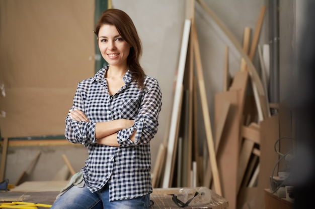 Happy girl carpenter in checkered shirt with arms crossed in workshop