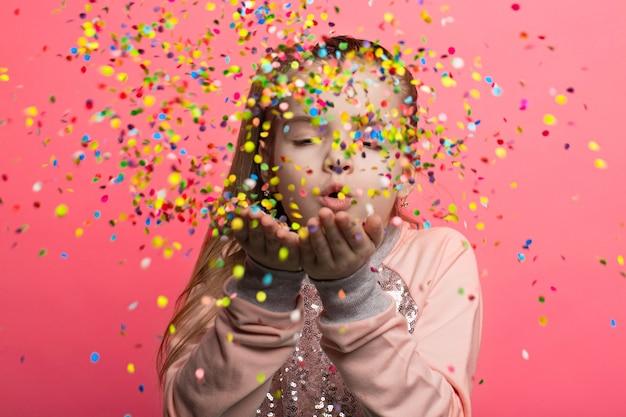 Happy girl celebrating. blows up multicolored confetti