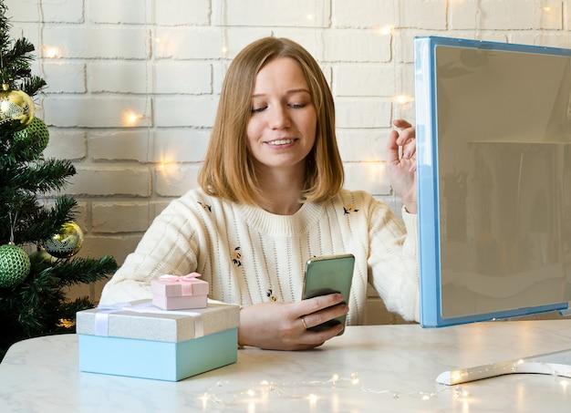 행복한 소녀는 스마트폰으로 친구들과 채팅합니다. 개념 온라인 크리스마스입니다.